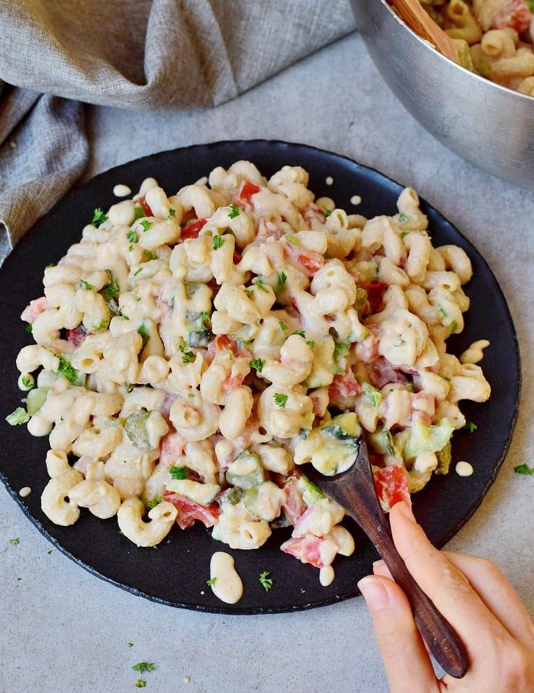 Veganer Nudelsalat mit Gemüse, ölfreiem Dressing (ohne Mayonnaise) auf einem schwarzen Teller