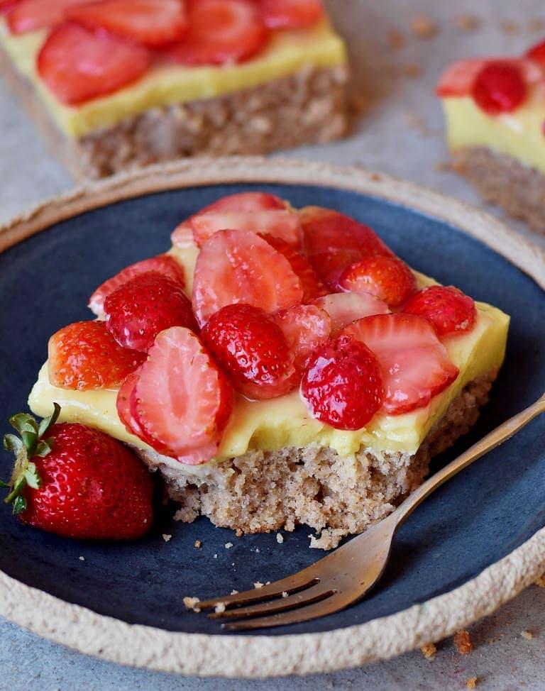 Ein Stück Erdbeerkuchen vom Blech mit Pudding auf einem Teller