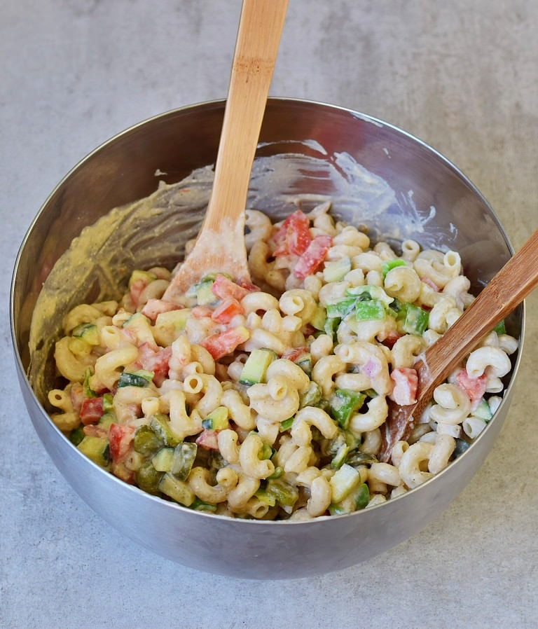 stirring homemade vegan pasta salad in a silver bowl