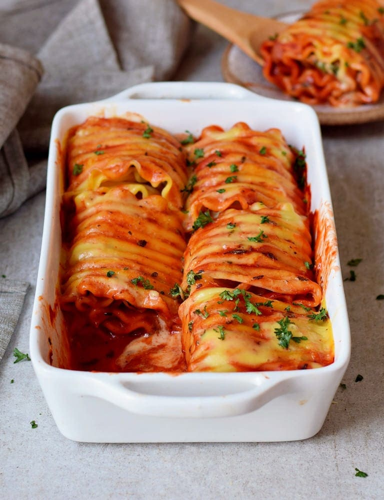 Vegan Lasagna roll ups in a baking dish stuffed with hummus