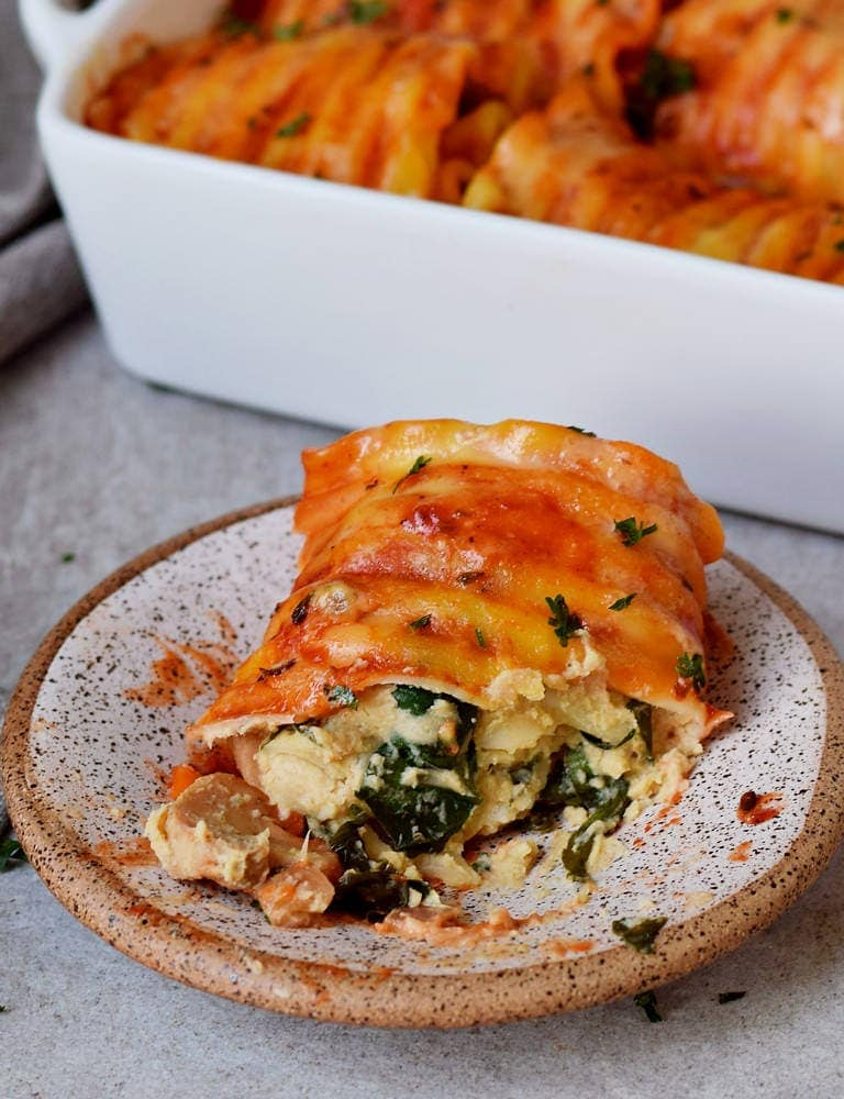 Vegetarian lasagna roll ups in a baking dish with vegan cheese