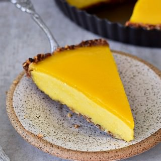 Mango cheesecake with vegan jelly and gluten-free granola crust on a plate
