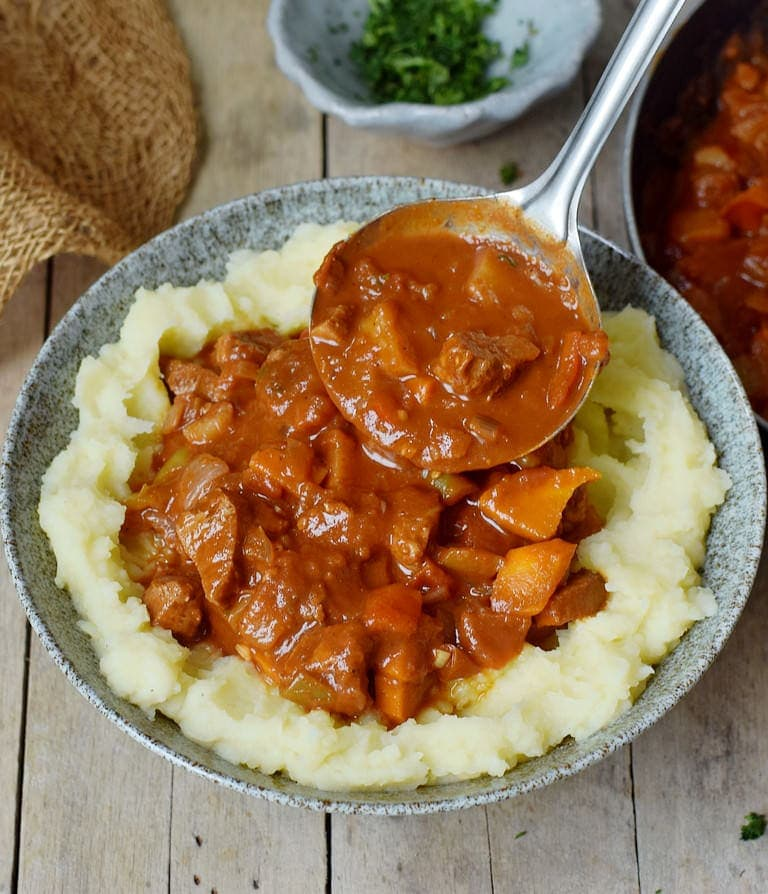 Hungarian vegan goulash over mashed potatoes with a ladle