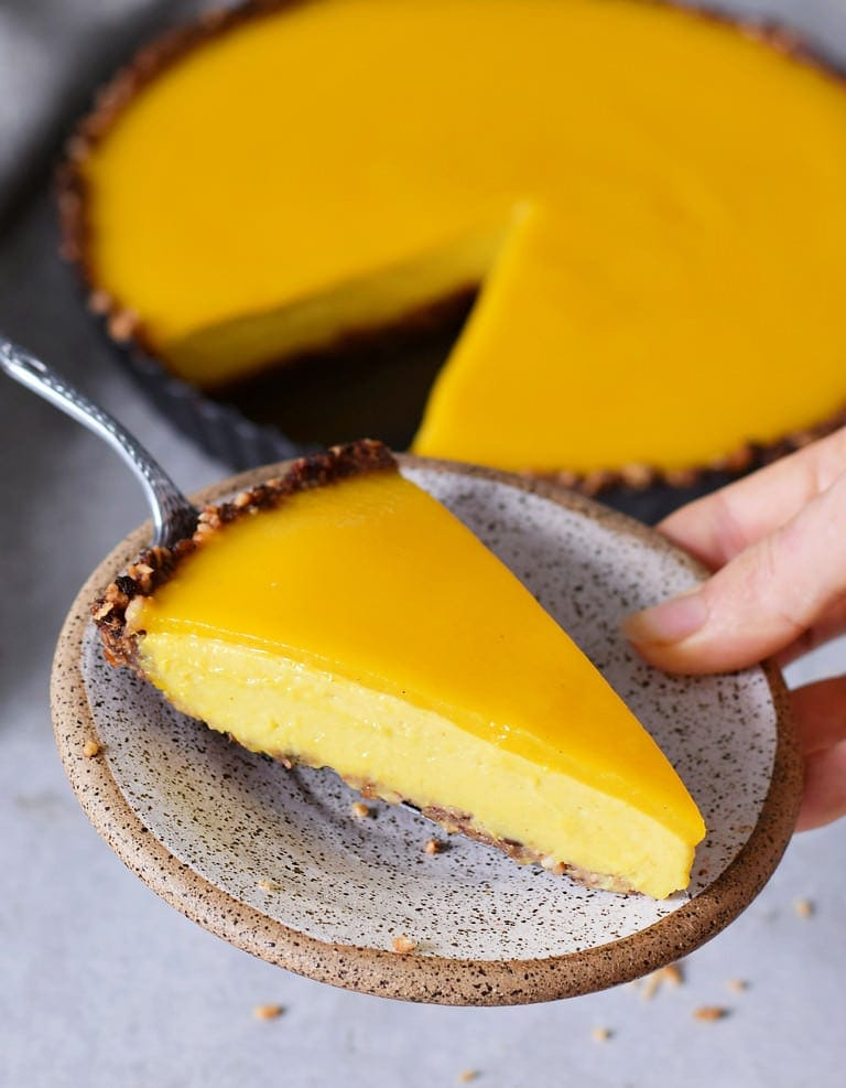 hand holding one piece of vegan mango cheesecake pie