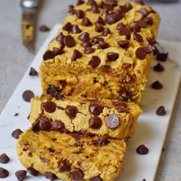 vegan pumpkin bread with chocolate chips on marble board