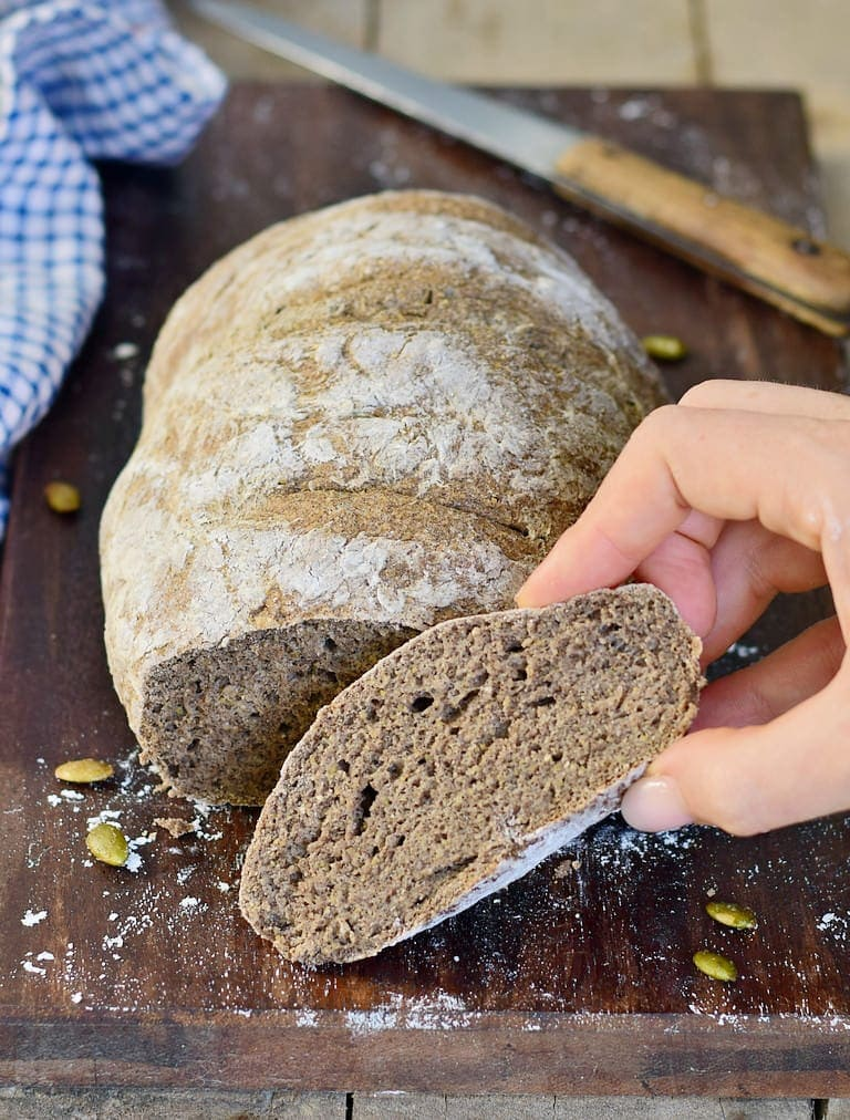 Hand hält ein Stück glutenfreies selbstgemachtes Brot