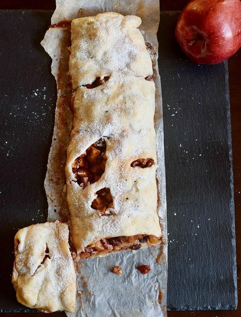 Veganer Apfelstrudel mit einem abgeschnitten Stück an der Seite