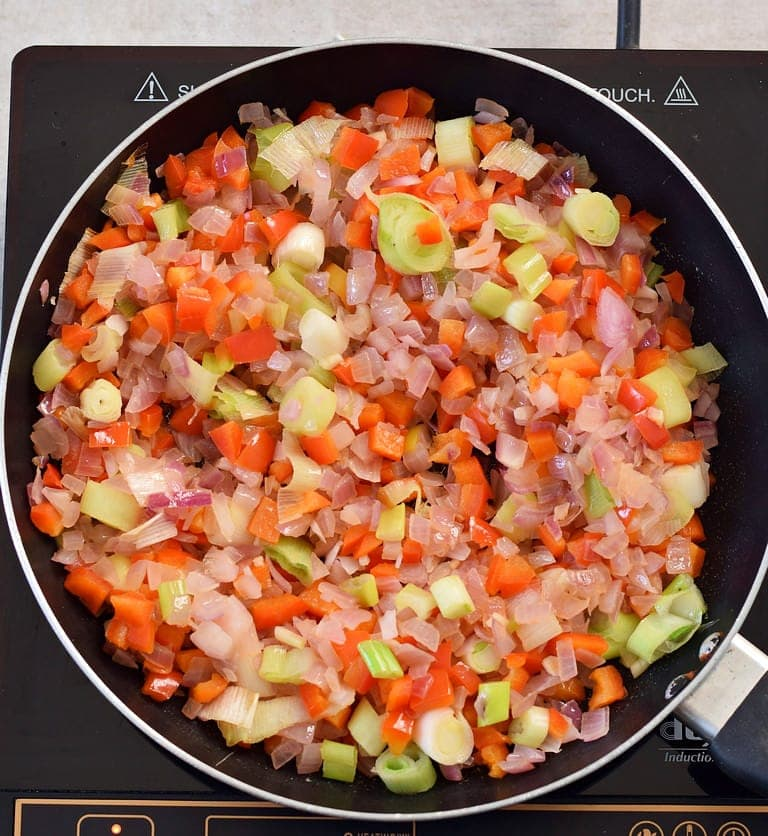chopped onion with leek and red pepper in a pan