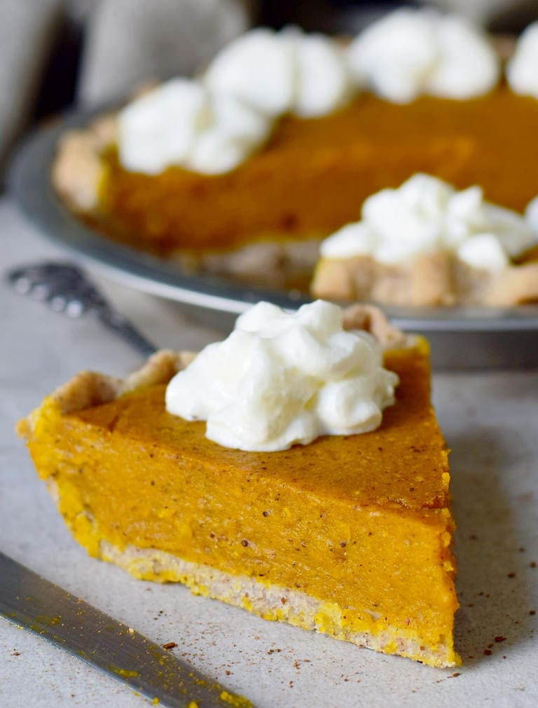 close-up of one vegan pumpkin pie piece with whipped cream