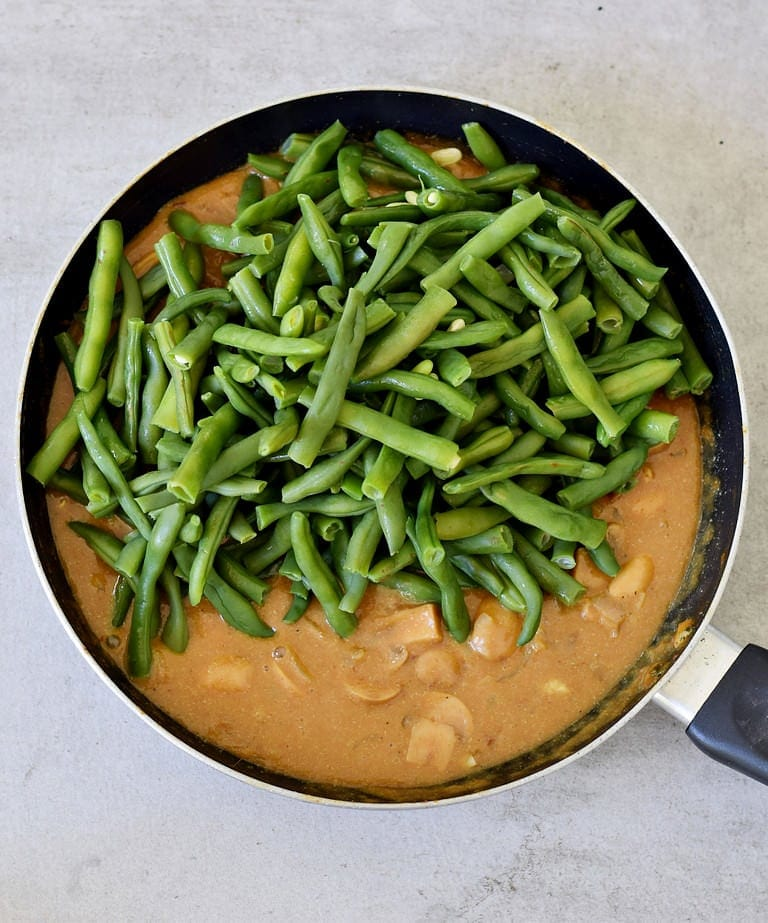 cooked green beans in a skillet with mushroom sauce