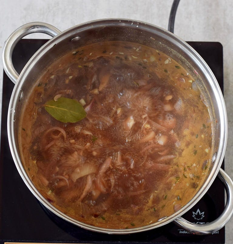 hearty soup with onions cooking in a big pot