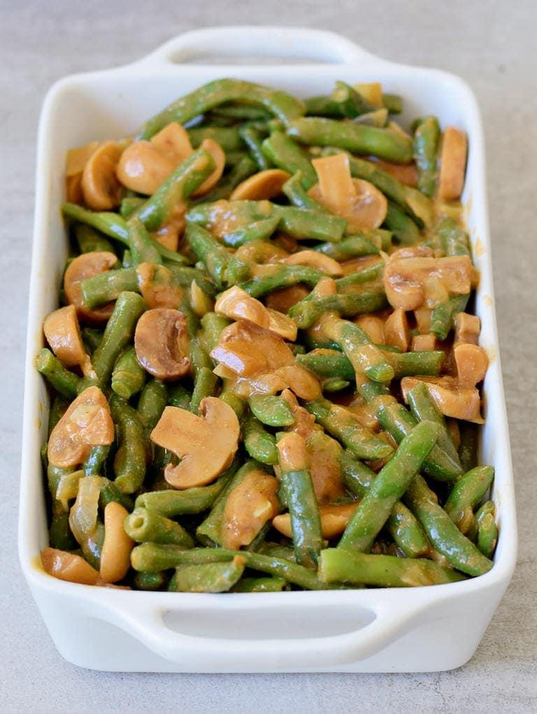 veganer grüner Bohnenauflauf vor dem Backen in einer weißen Auflaufform