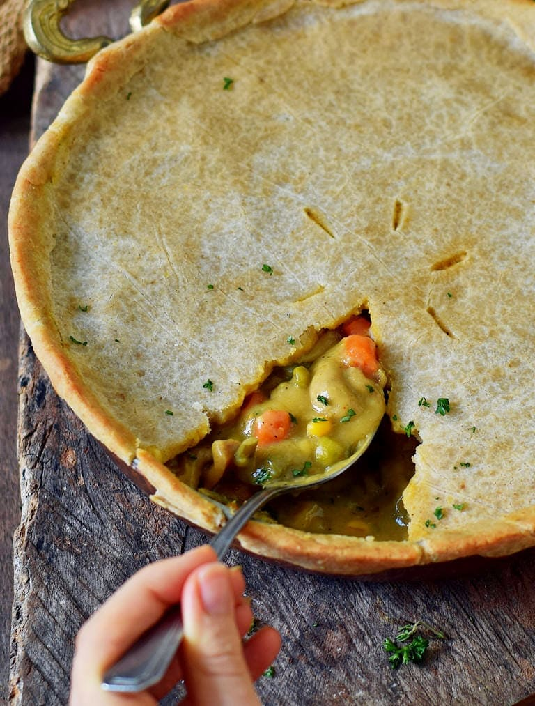 hand holding a spoon submerged in a vegetable pie