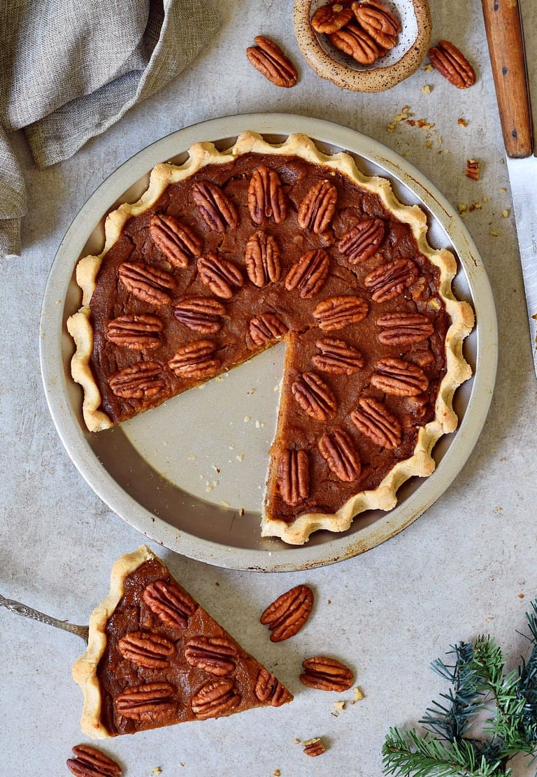 vegan pecan pie from above with a piece cut out