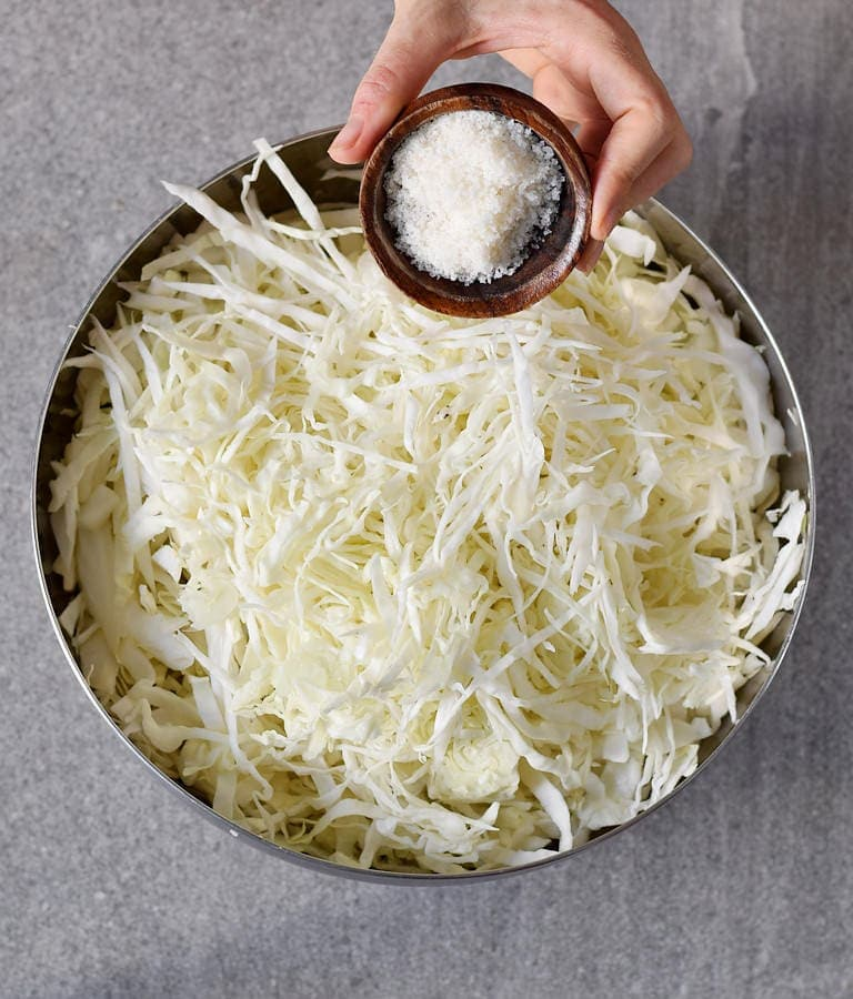 Adding salt to shredded white cabbage in a bowl