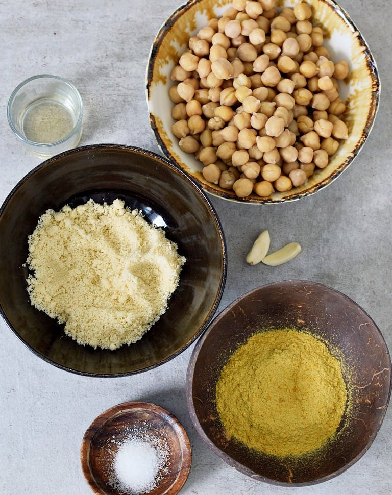 Chickpeas, almond flour, nutritional yeast, lemon juice, salt, garlic on a gray backdrop
