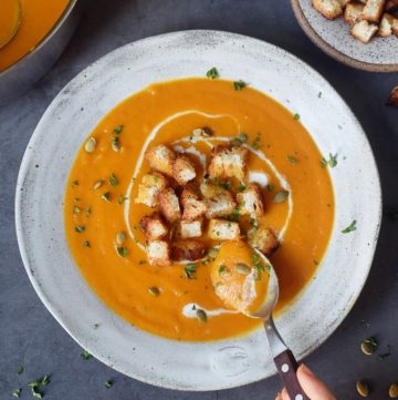 Eating carrot soup with croutons and pumpkin seeds