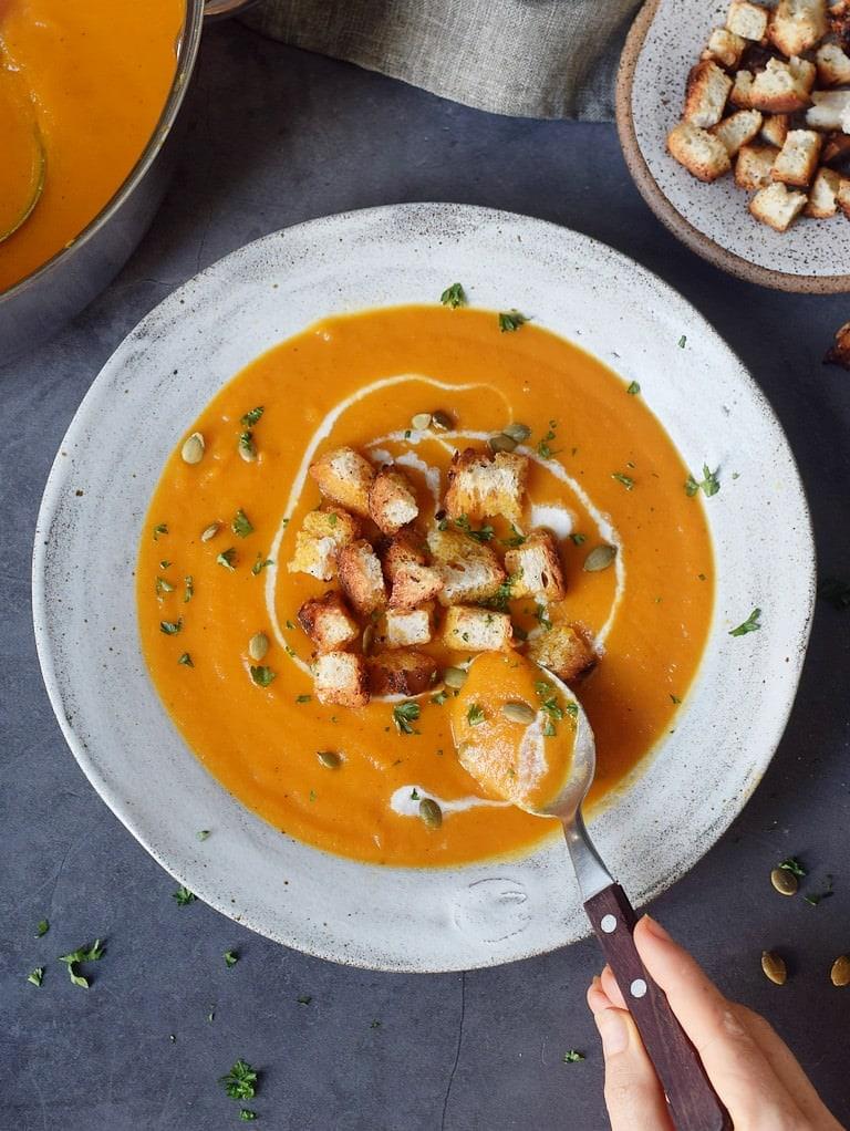 Essen einer cremigen Karottensuppe in einer grauen Schale mit Croutons