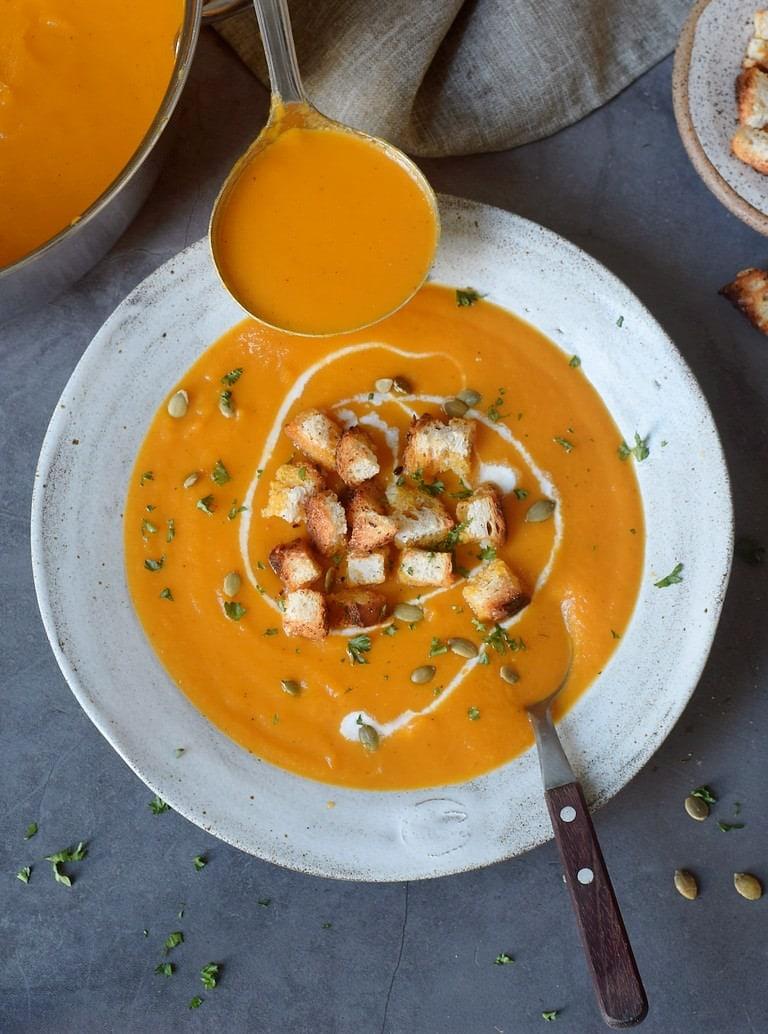Vegane Karottensuppe in einer grauen Schüssel mit Croutons, Löffel und Schöpfkelle