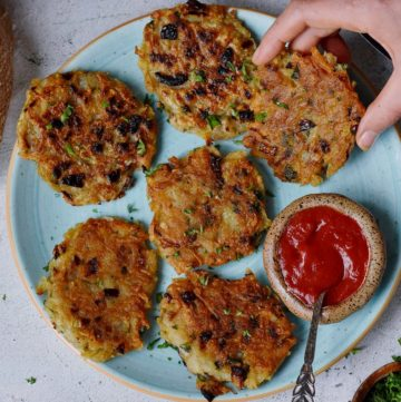 hand grabbing one of 6 vegan potato pancakes on a cyan plate