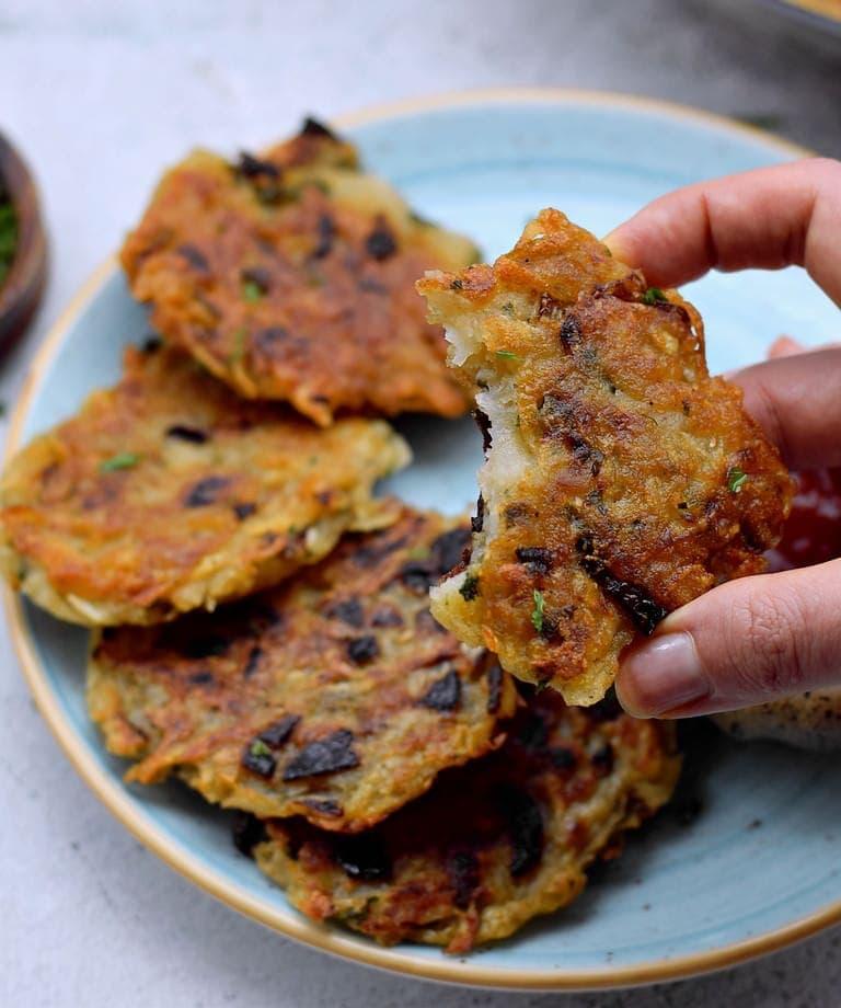 hand holding one of 5 crispy rosti on plate