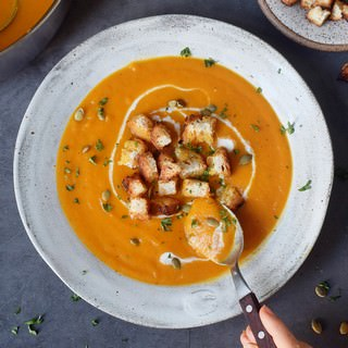orange soup with carrots in a gray bowl with spoon