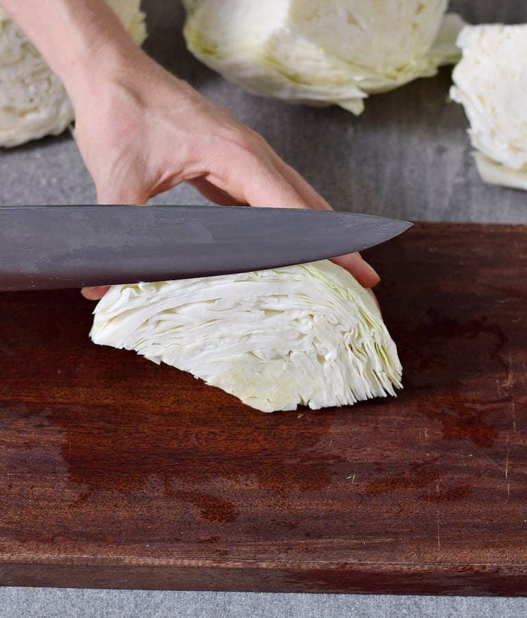 slicing white cabbage with a large knife on a wooden board