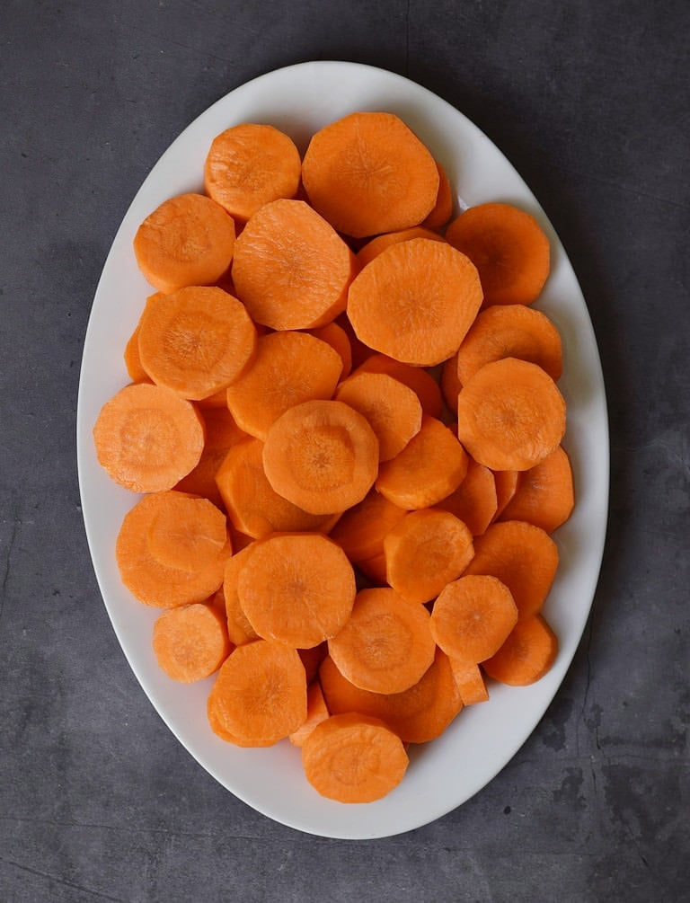 Weißer ovaler Teller mit vielen Karottenscheiben