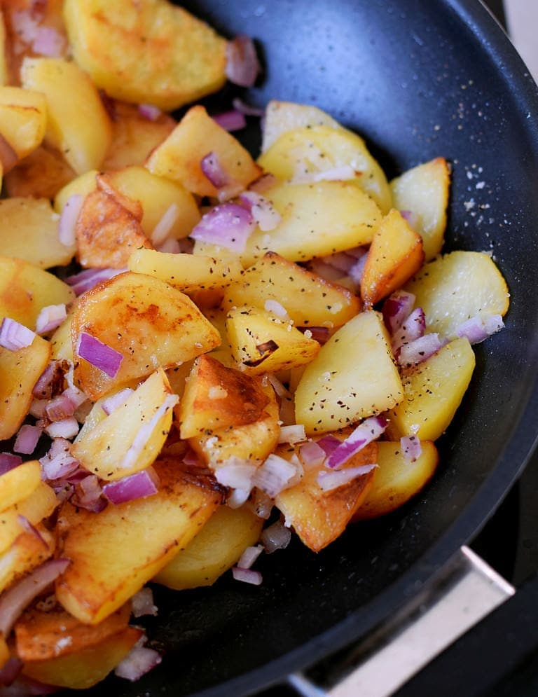 close up of roast potato slices in a frying pan