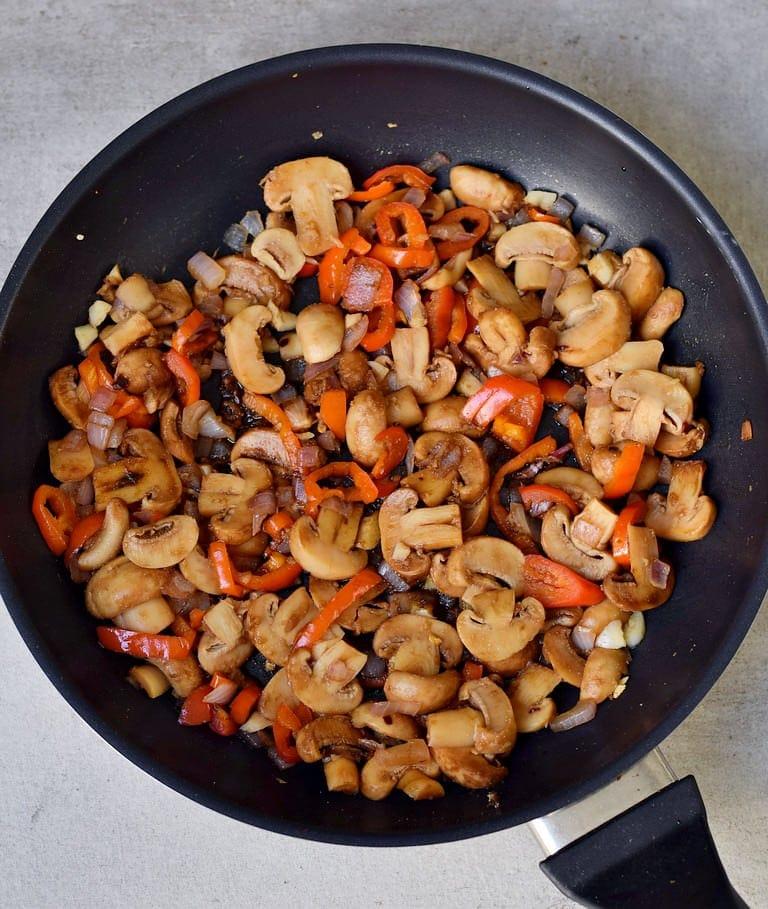 Angebratene Pilze, Paprika und Zwiebeln in einer schwarzen Pfanne