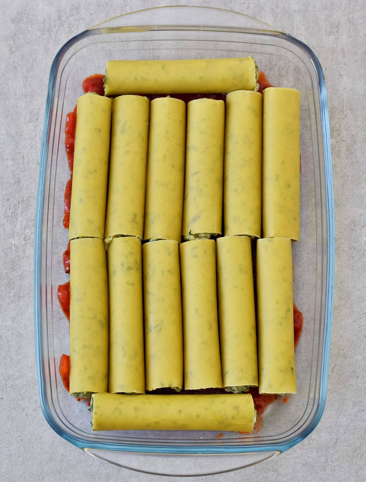 14 ricotta and spinach cannelloni tubes in a casserole dish