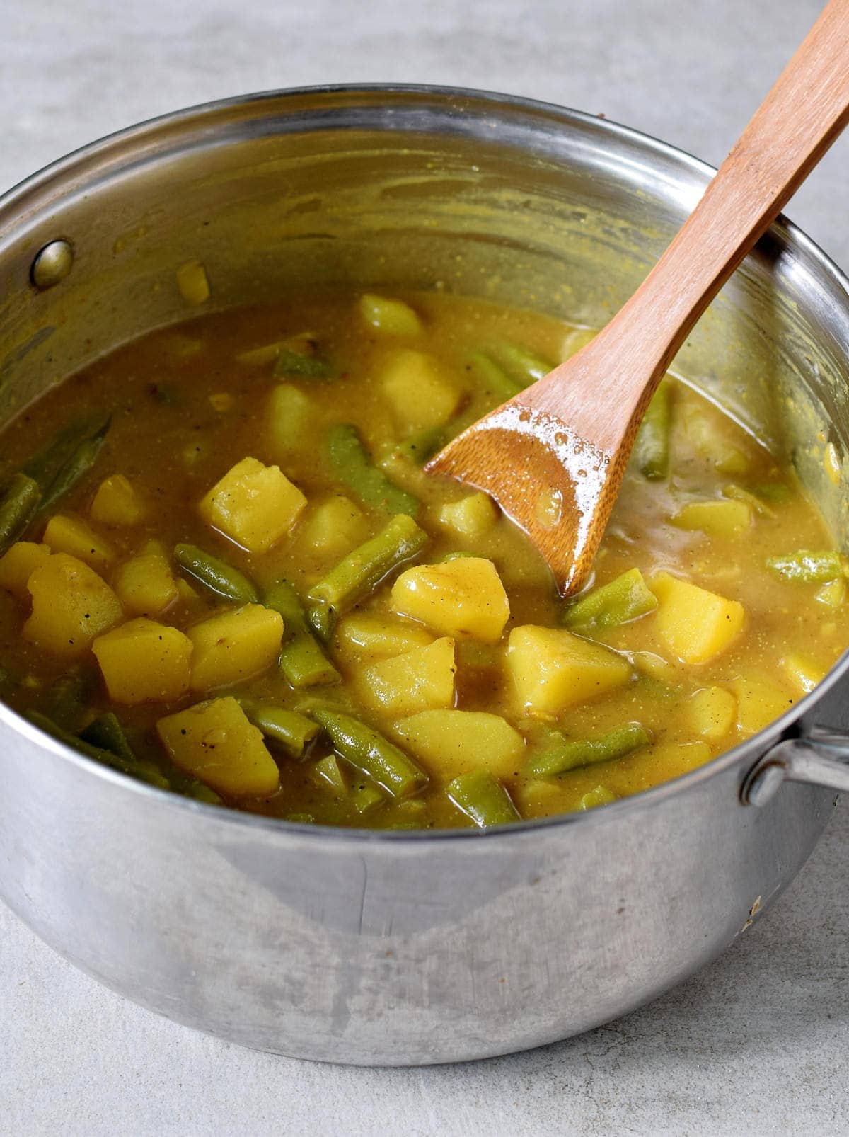aloo curry with green beans in a large pot with a wooden spoon