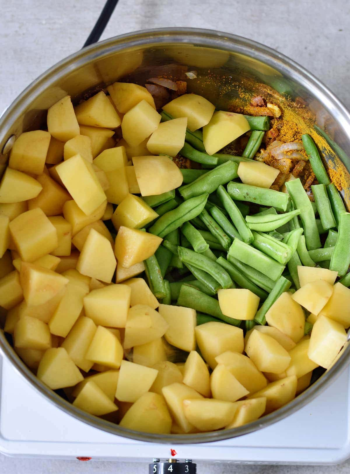 chopped potatoes green beans and spices in a pot