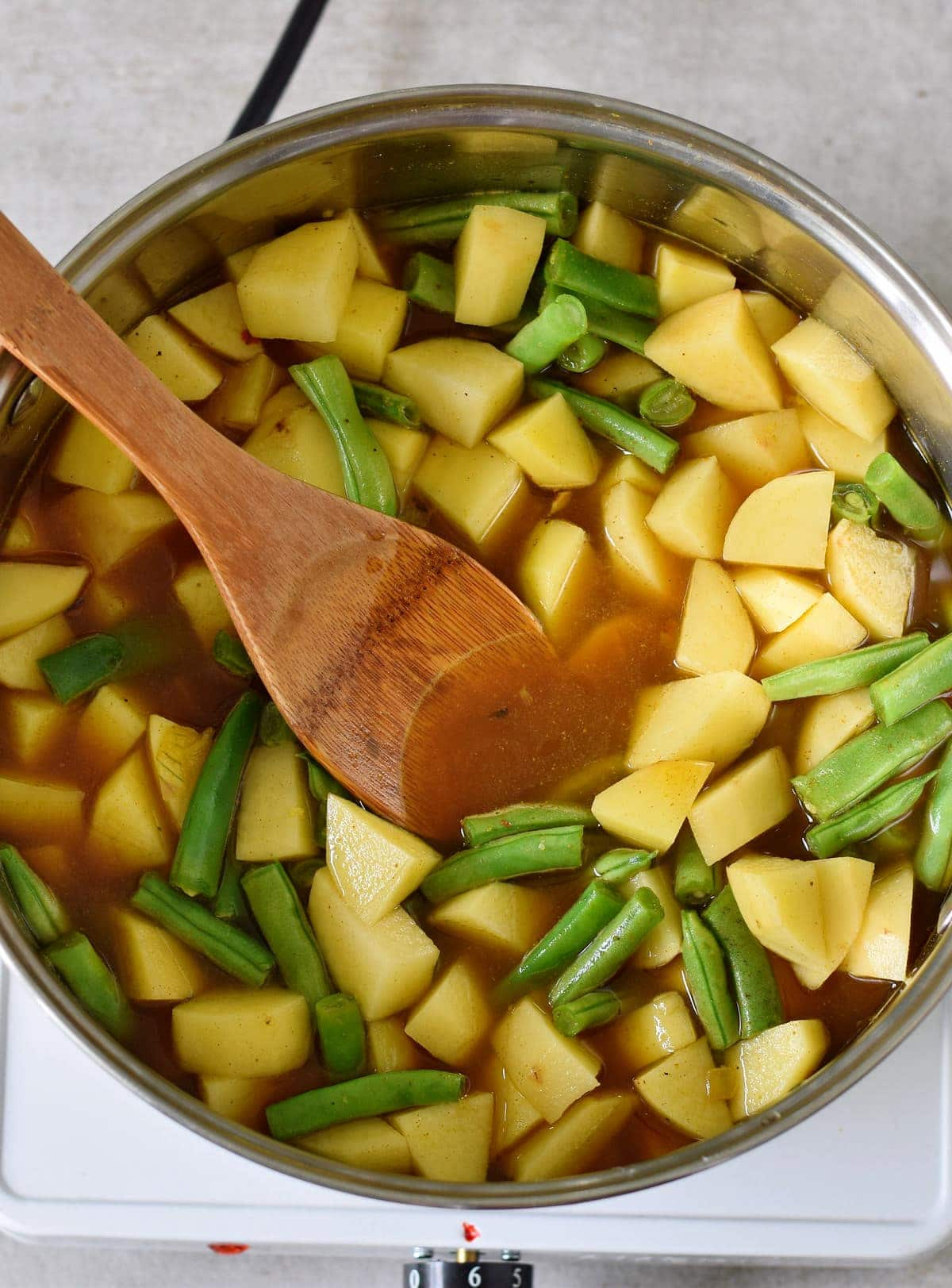 chopped potatoes green beans and vegetable broth in a pot