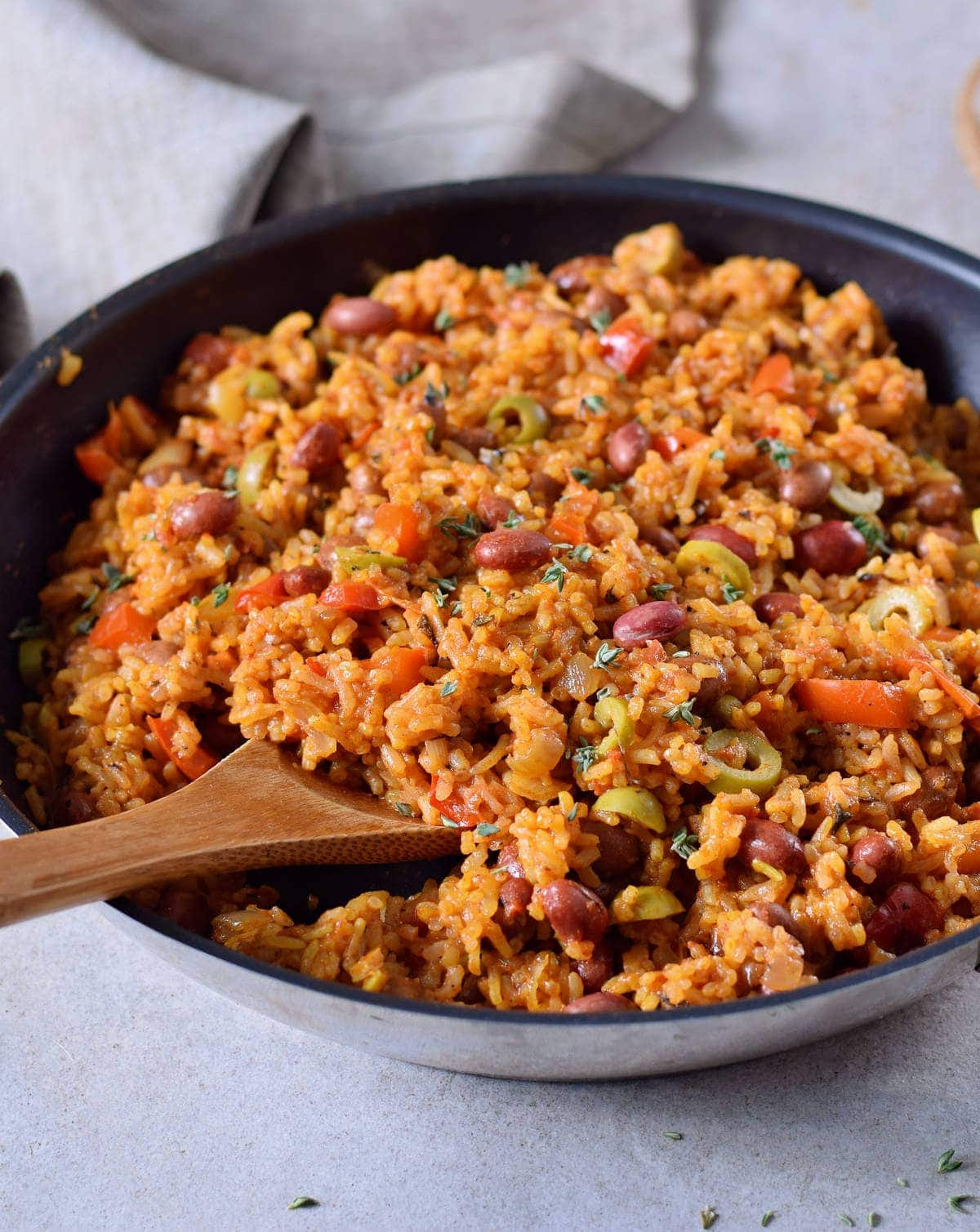 close-up of Spanish rice and beans with olives in a pan