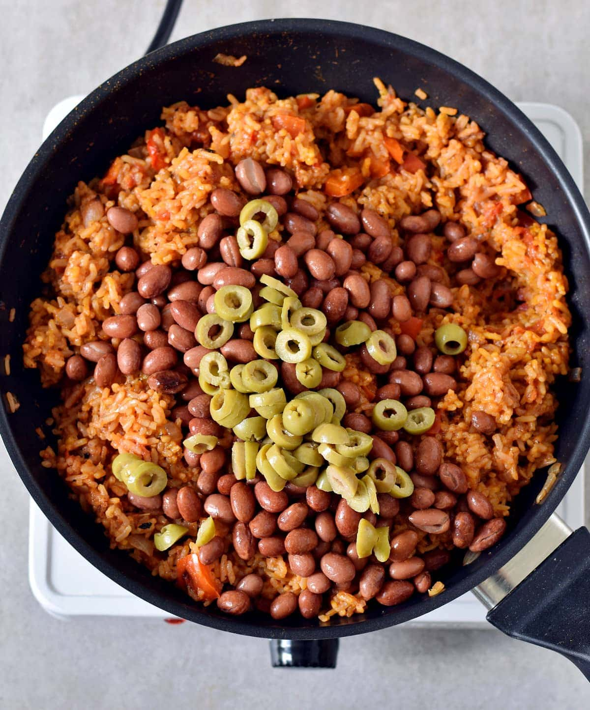 cooked rice with red beans and olives in a pan