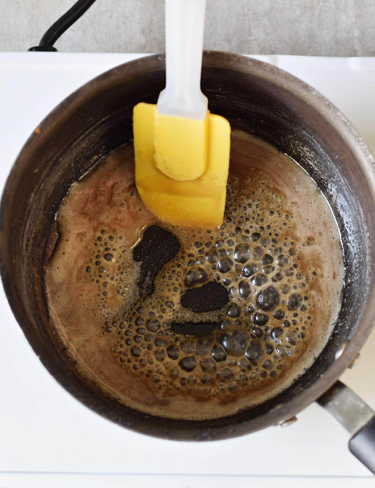 cooking caramel in a black saucepan with a yellow spatula