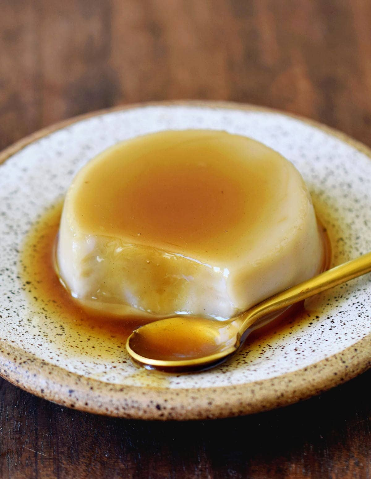 eating vegan flan with caramel on a plate with golden spoon