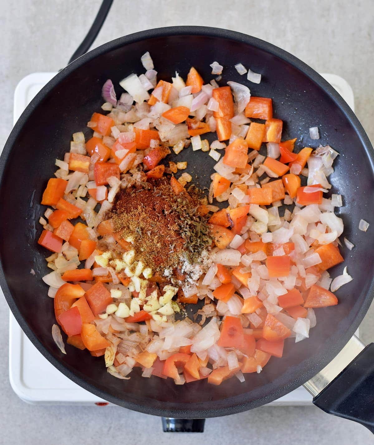 onion and red pepper with spices in a pan