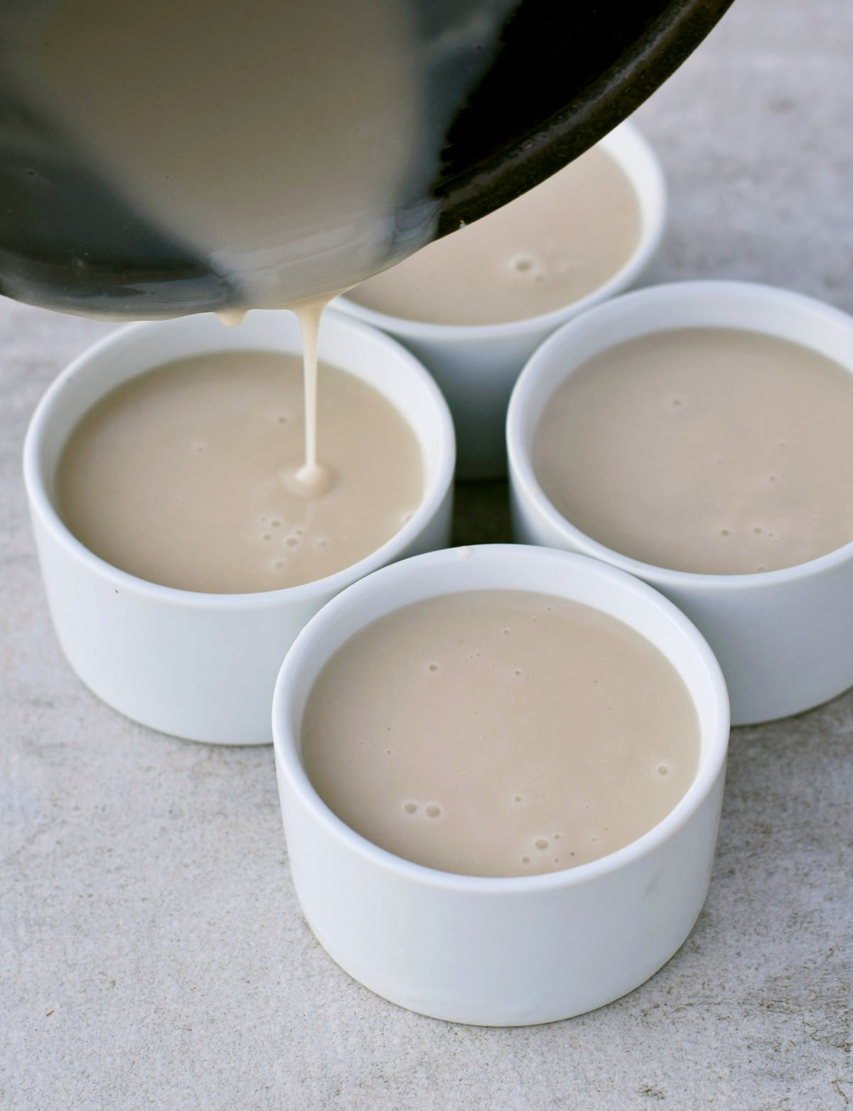 pouring vegan custard in 4 white ramequins