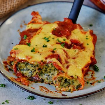 three spinach and ricotta stuffed cannelloni with vegan cheese