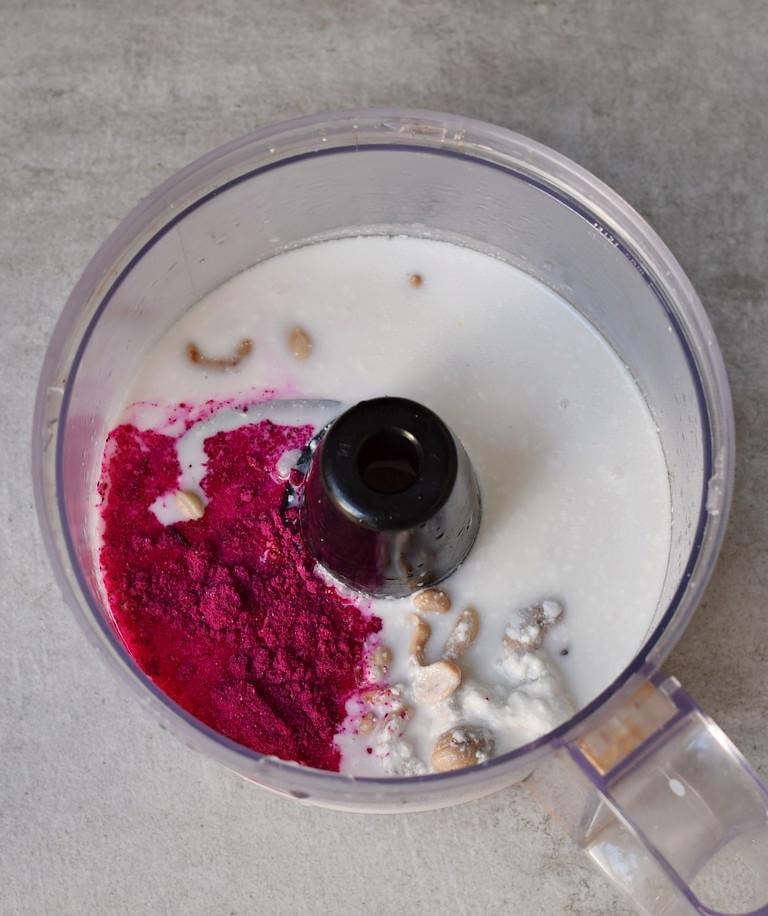 feuchte Zutaten für rosanen Käsekuchen in einem Zerkleinerer