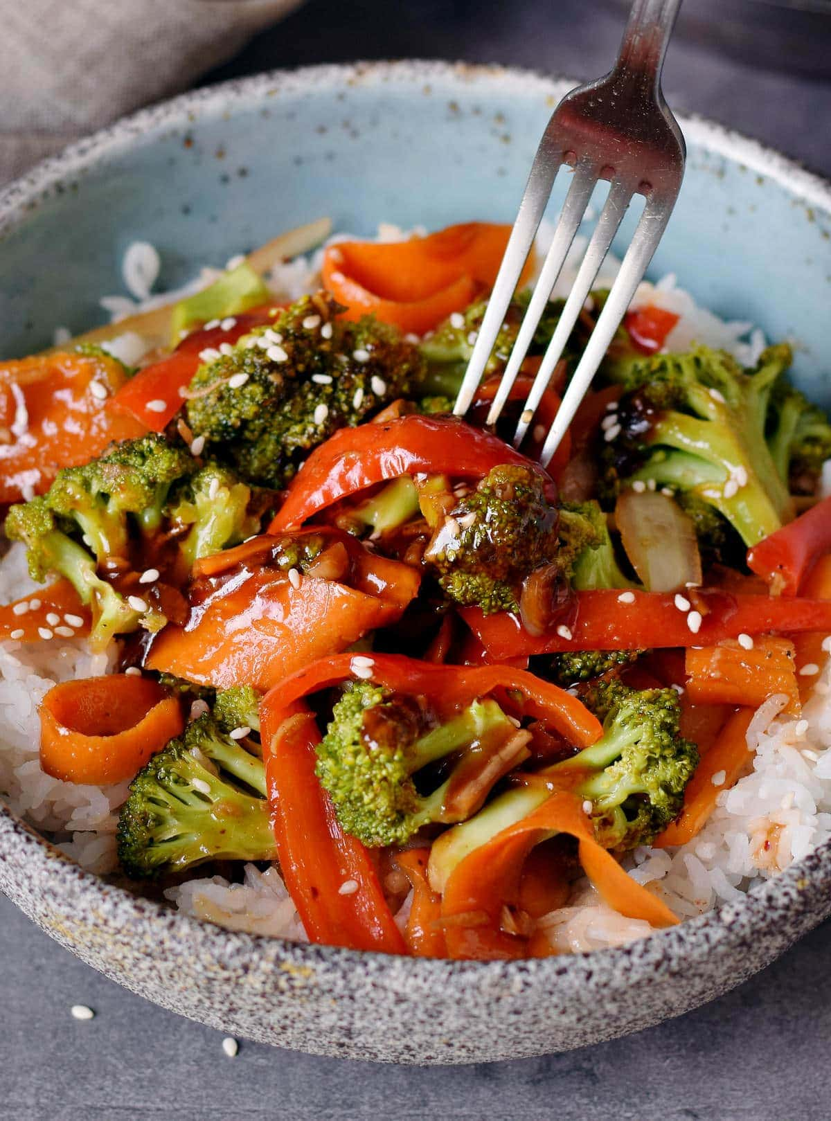 fork submerged in broccoli stir-fry with rice