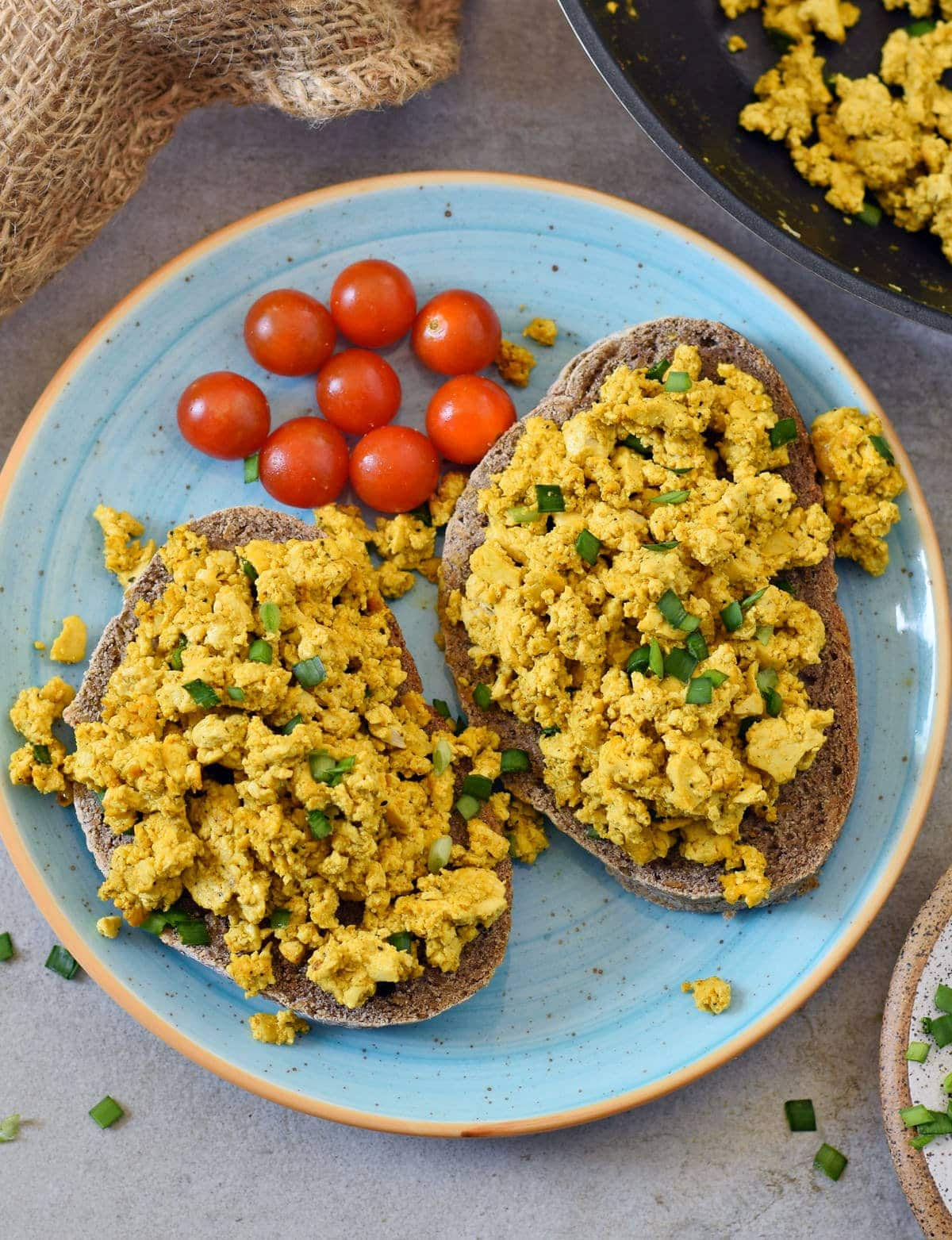 tofu scramble on gluten-free bread with cherry tomatoes on the side