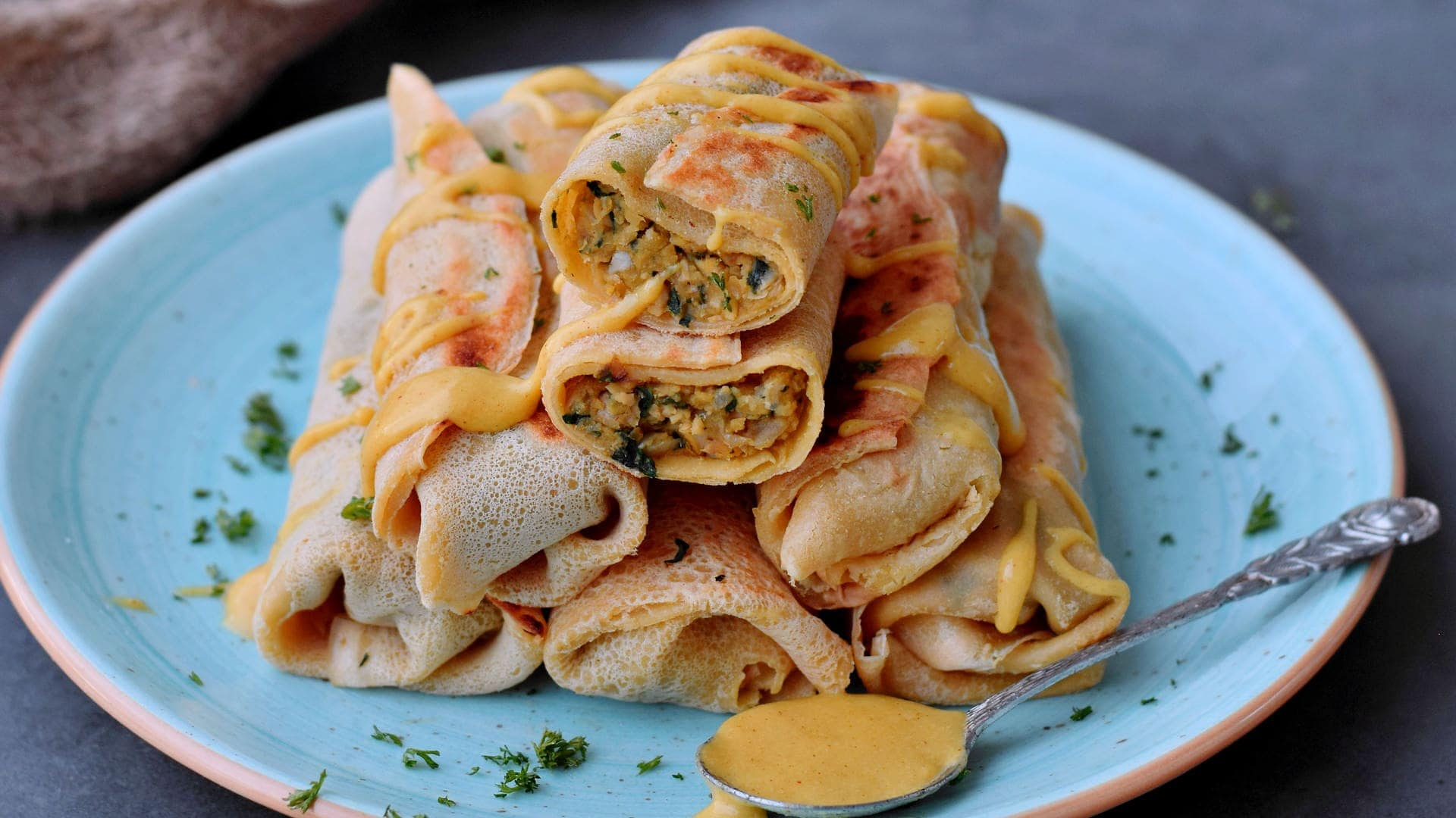 6 homemade savory crepes on a turquoise plate with vegan cheese sauce