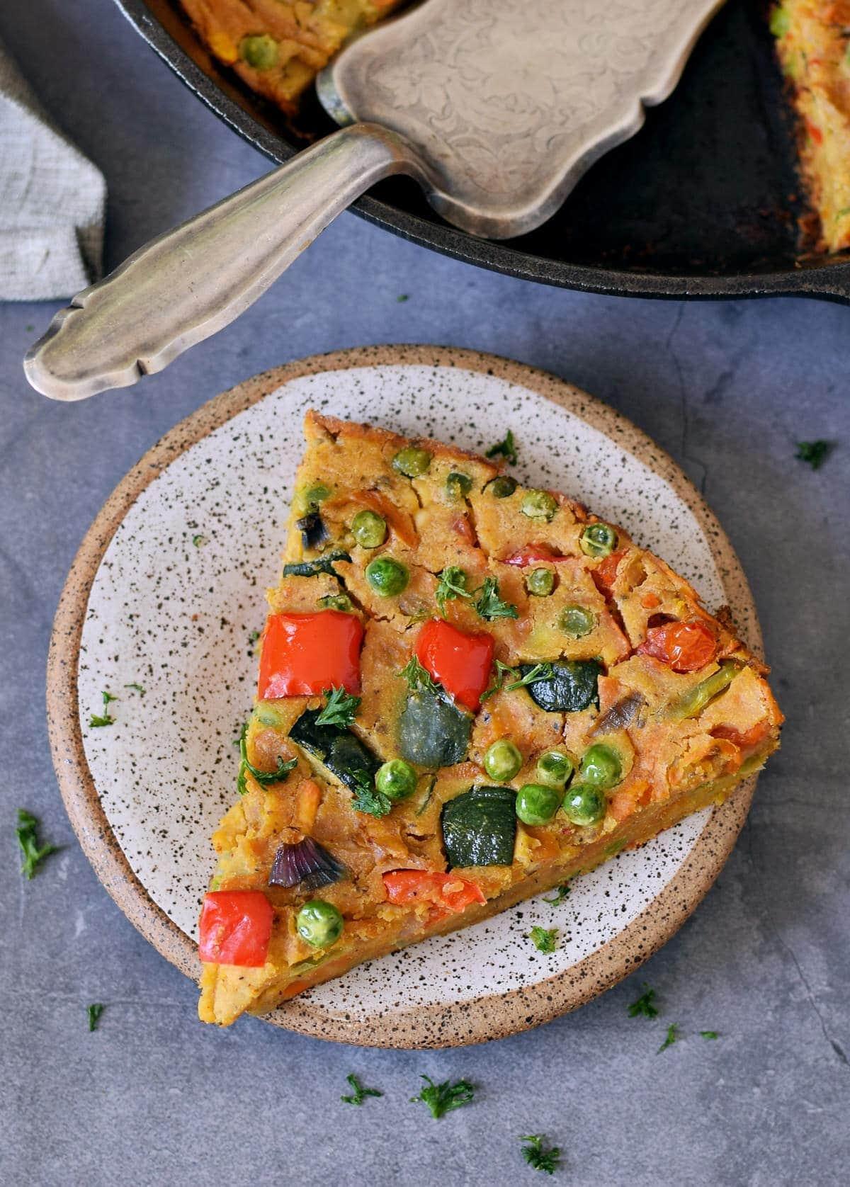 Ein Stück Gemüse Frittata auf Teller von oben