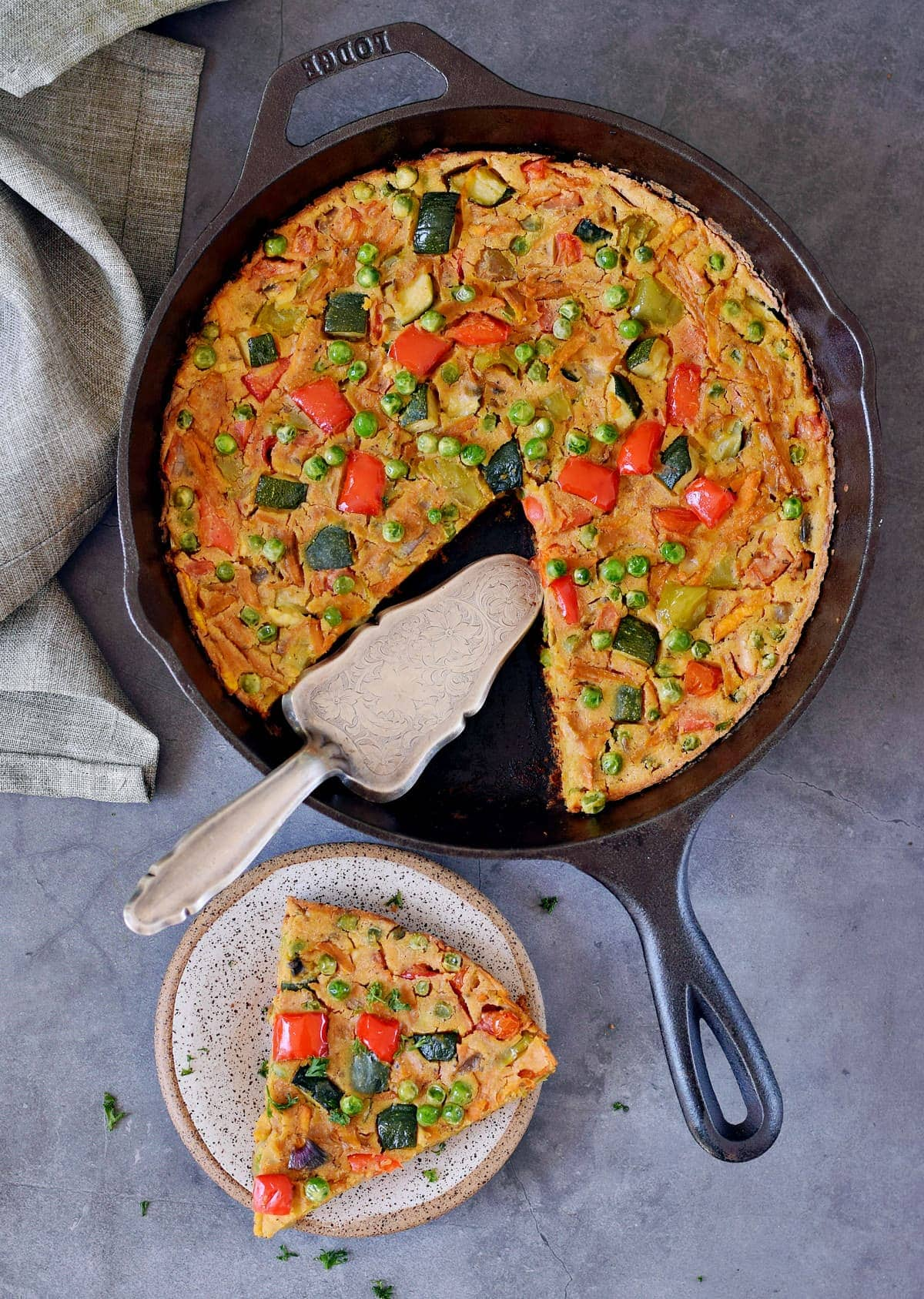 Bird view of vegan frittata in a black skillet with a piece on a small plate