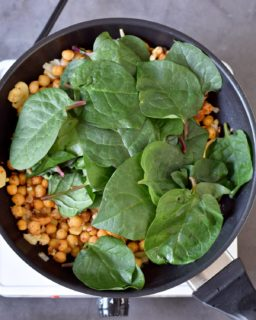 Chickpeas, and spinach in a black pan