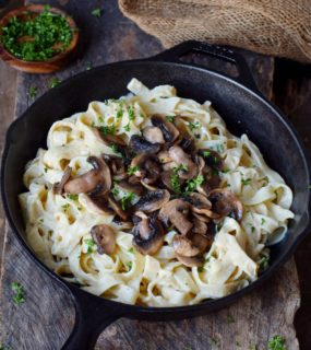 Creamy Fettuccine Alfredo with mushrooms in a black skillet