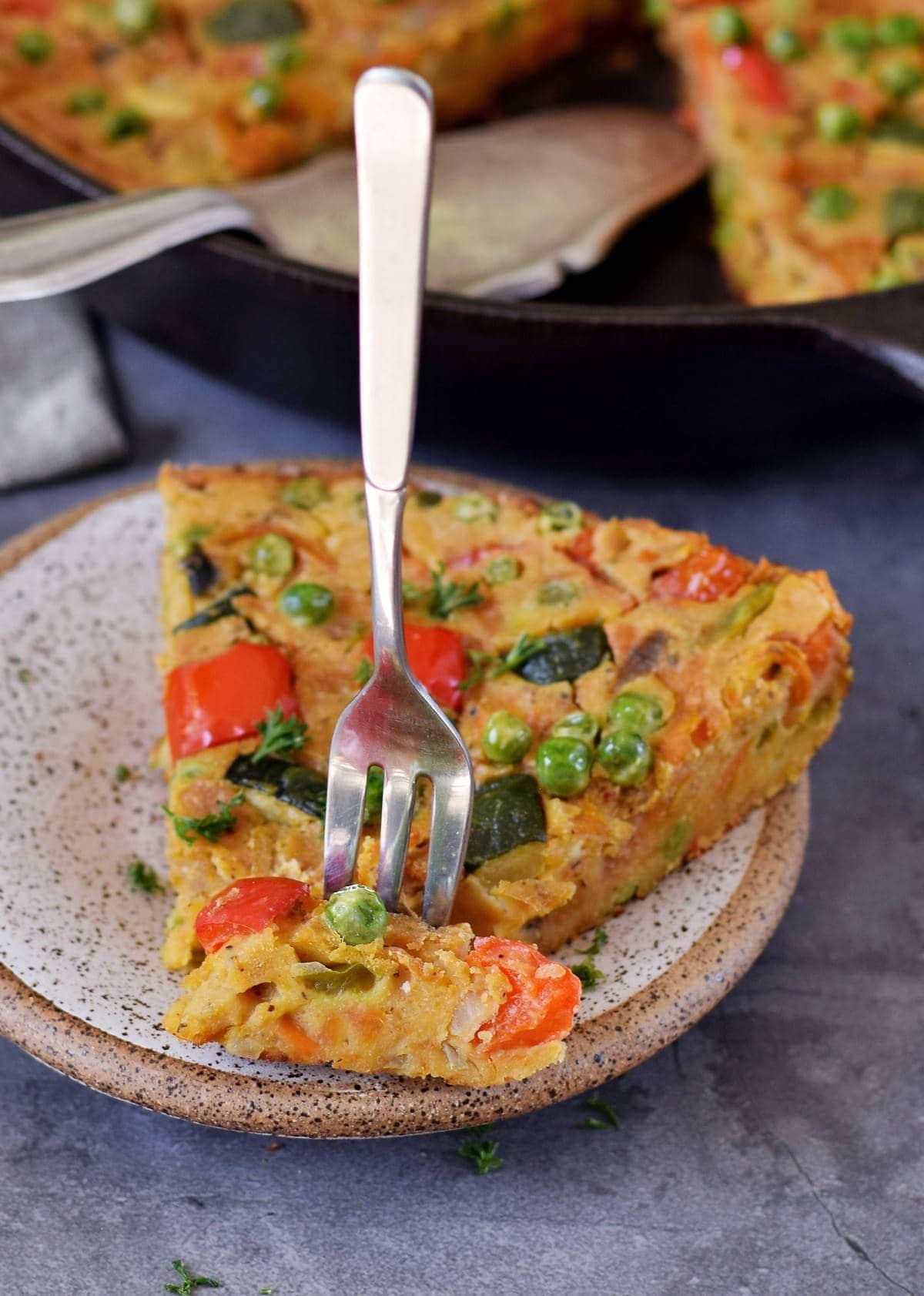 Ein Stück vegane Gemüse Frittata auf Teller mit Gabel